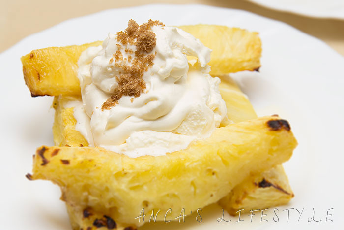 Pineapple dessert: grilled pineapple with whipped cream and sugar on top.