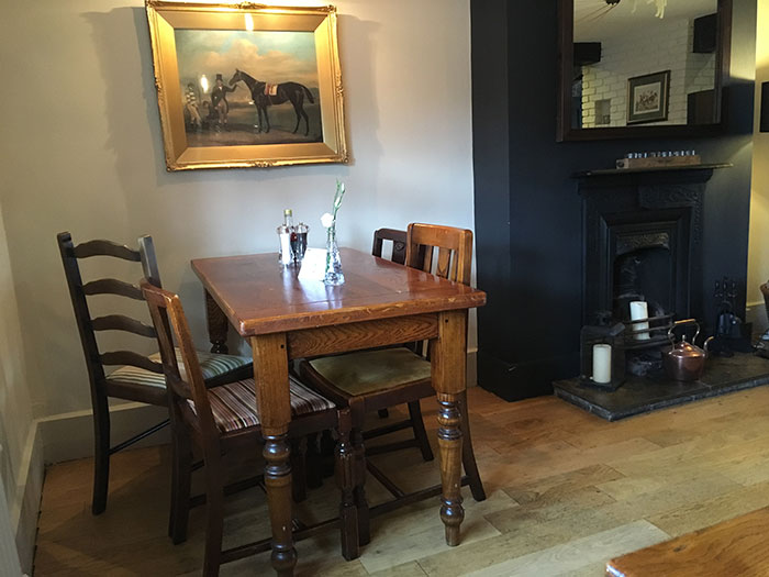 Table, picture with a horse and the fireplace beside them